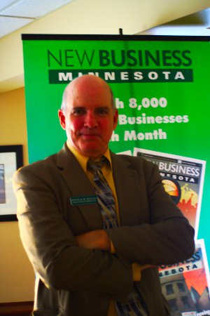 Patrick Boulay, publisher of the New Business Minnesota monthly magazine, poses in front of a company promotional banner at a recent meet-up honoring heroes of the business start-up community in Minnesota.